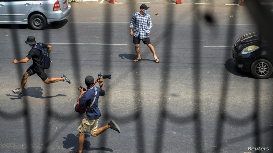 FILE - Pro-democracy protesters and a journalist run as riot police officers advance them during a rally against the military coup in Yangon, Myanmar, Feb. 27, 2021.