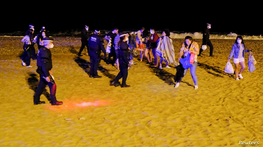 Police officers evict groups of more than six people at Barceloneta beach in Barcelona, Spain, May 16, 2021.