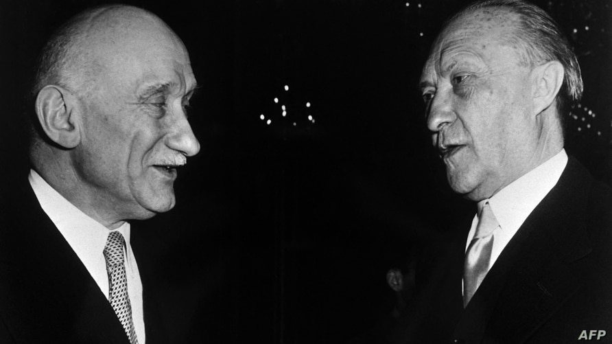 French Foreign Minister Robert Schuman (L) and German Chancellor Konrad Adenauer (R) chat during the reception wich followed…