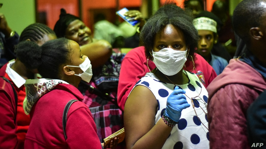 Travellers wearing face masks as protective measure wait to get their temperature checked at the border post with Kenya in…