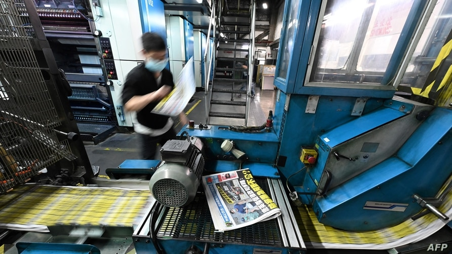 This photo taken on May 11, 2021 shows an employee working at the printing facility of the Apple Daily newspaper in Hong Kong. …