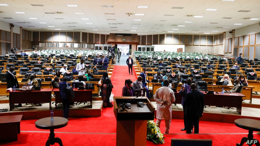 Pan African Parliament members gather in groups inside the house following its postponement in Midrand, Johannesburg on June 1,…