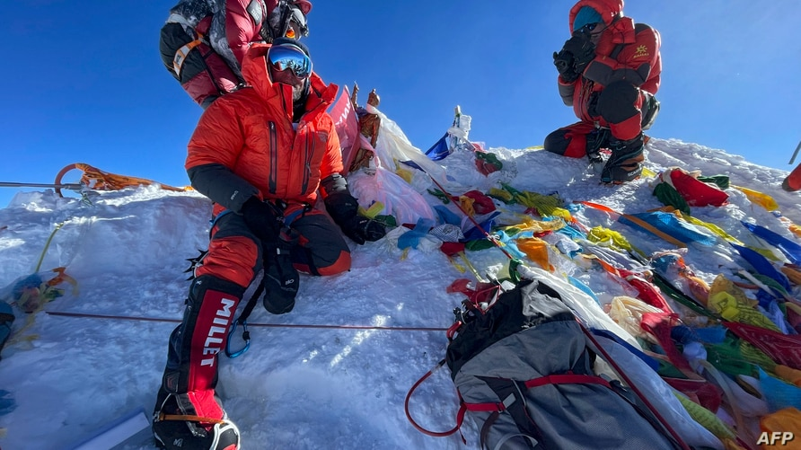 This photograph taken on May 31, 2021 shows mountaineers at the summit of Mount Everest (8,848.86-metre), in Nepal. (Photo by…