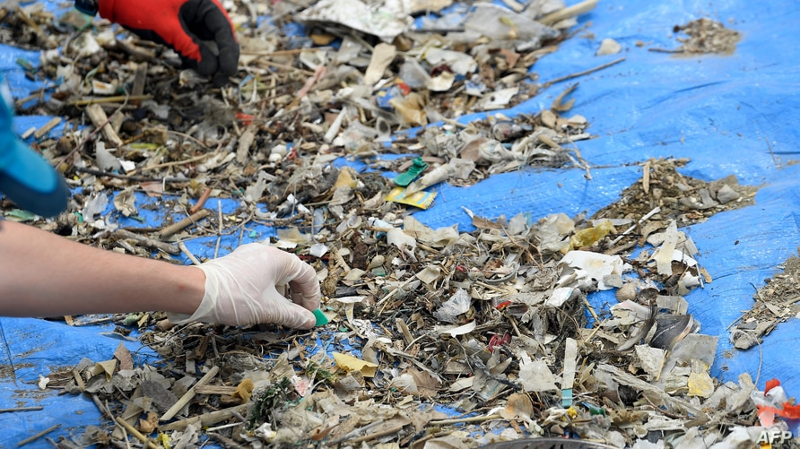 Volunteers sort micro-plastic waste collected on an island of the Etang de Berre during a clean-up operation at the initiative…