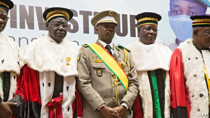 New interim Malian President, Colonel Assimi Goita (C), stands with members of the Supreme Court during his swearing in…