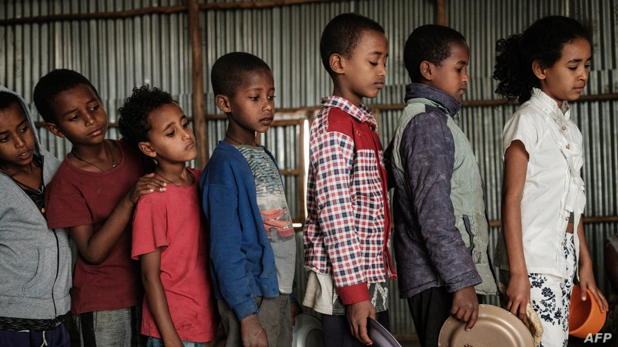 Children, who fled the violence in Ethiopia's, Tigray region, wait in line for breakfast organized by a self-volunteer Mahlet…