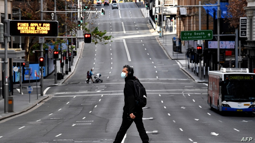 A man walks along the main road in the central business district of Sydney on June 26, 2021, as Australia's largest city…