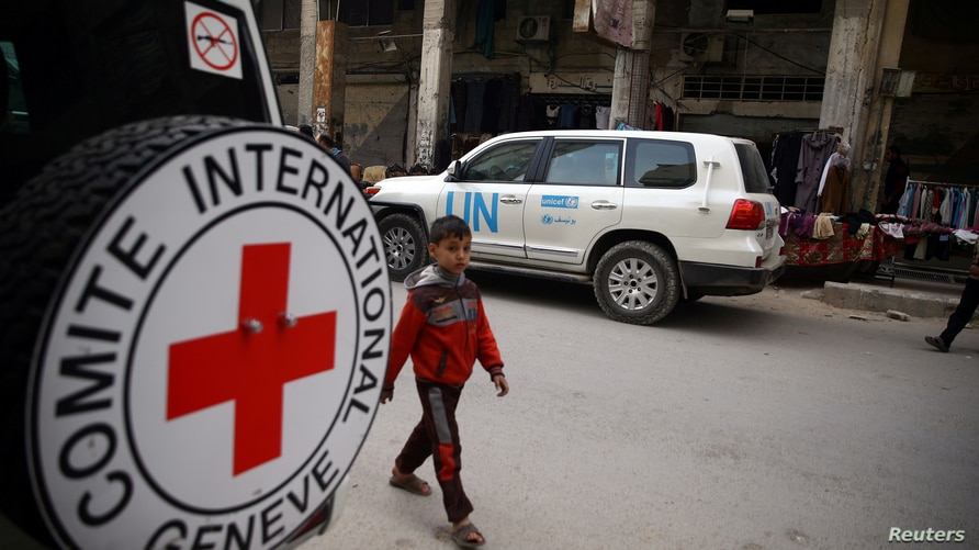 A Syrian child is seen walking near International Red Cross vehicle in the rebel-held city of Douma, in the eastern Damascus…