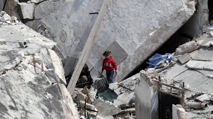 A girl stands near a woman on the rubble of a damaged building in the rebel-held town of Nairab, in northwest Syria's Idlib…