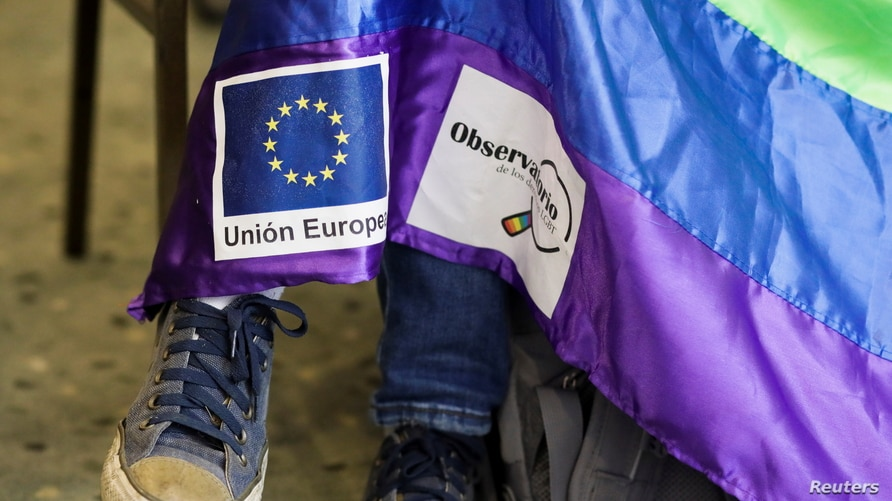 A member of LGBT movement holds a flag with signs of European Union and LGBT rights during a news conference where the first…