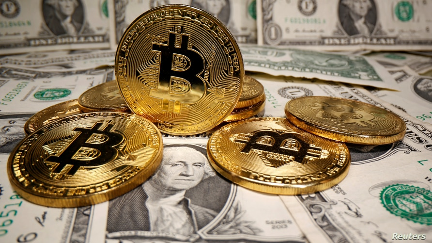FILE - Representations of virtual currency Bitcoin are placed on U.S. Dollar banknotes in this illustration taken May 26, 2020.