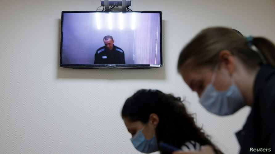 Russian opposition leader Alexei Navalny is seen on a screen via a video link during a hearing to consider his lawsuits against the penal colony over detention conditions there, at the Petushki district court in Petushki, Russia, May 26, 2021.