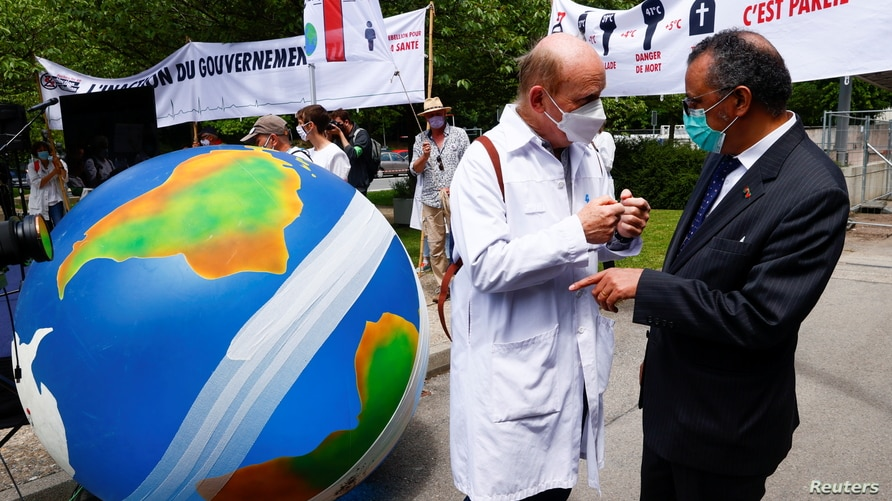 A member of Doctors for XR (Extinction Rebellion) speaks with World Health Organization (WHO) Director General, Tedros Adhanom Ghebreyesus, during a demonstration urging him to take action on climate change, in Geneva, Switzerland, May 29, 2021.