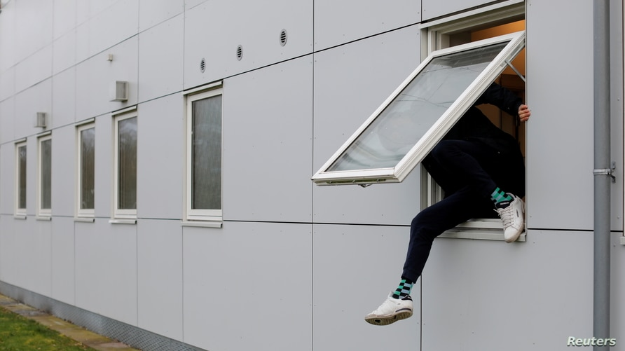FILE - A resident climbs through a window at Kaershovedgaard, a former prison and now a departure centre for rejected asylum seekers in Jutland, Denmark, March 26, 2019.