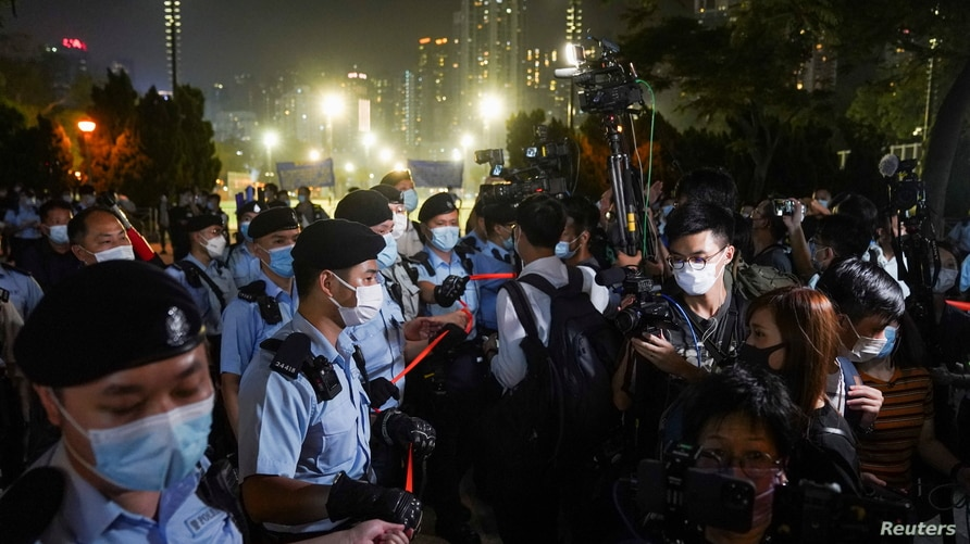 People look at police officers standing guard at Victoria Park on the 32nd anniversary of the crackdown on pro-democracy…