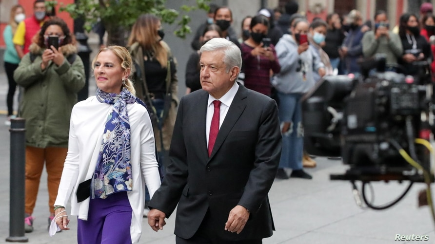 Mexico's President Andres Manuel Lopez Obrador and his wife Beatriz Gutierrez walk at a polling station during the mid-term…