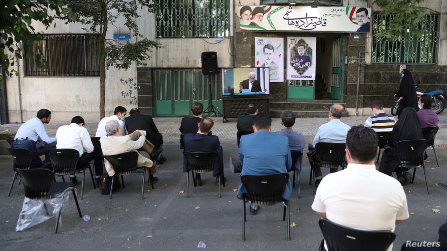 People watch the debate of presidential candidates on a street in Tehran, Iran June 8, 2021. Majid Asgaripour/WANA (West Asia…
