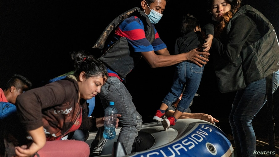 Asylum-seeking migrant families disembark an inflatable raft after crossing the Rio Grande river into the United States from Mexico in Roma, Texas, June 9, 2021.