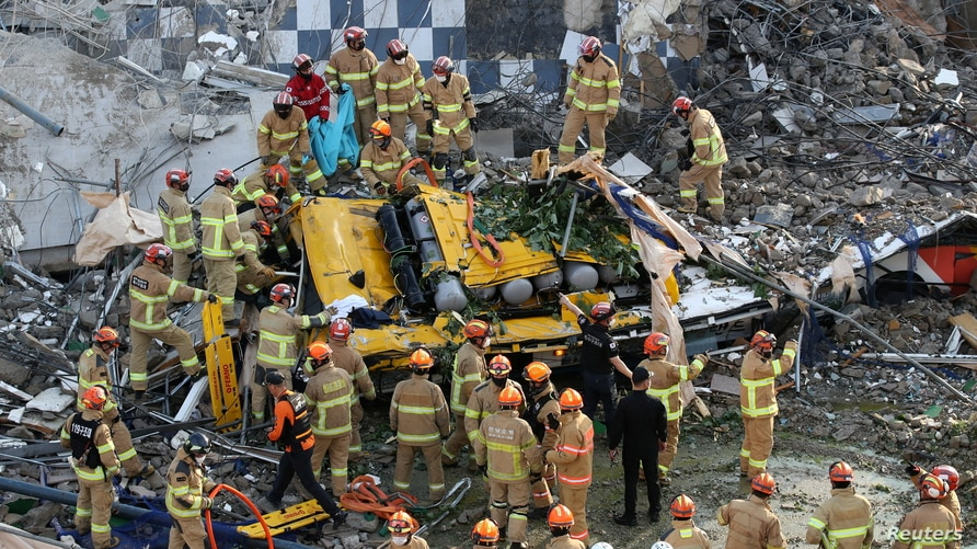 South Korean firefighters search for passengers from a bus trapped by the debris of a collapsed building in Gwangju.