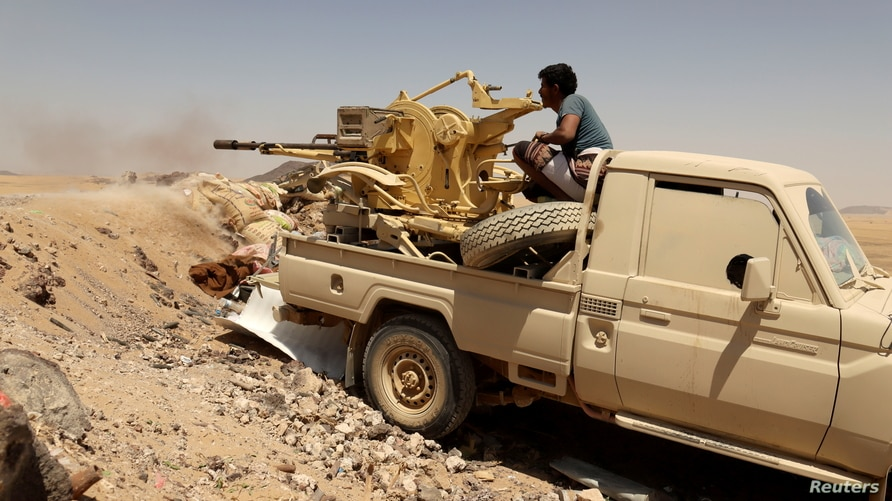 FILE PHOTO: A Yemeni government fighter fires a vehicle-mounted weapon at a frontline position during fighting against Houthi…