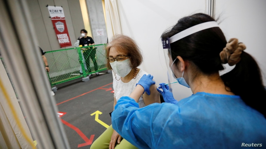 A woman receives a dose of the COVID-19 vaccine at the Noevir Stadium Kobe, the home venue of Japanese professional soccer club Vissel Kobe and currently acting as a large-scale COVID-19 vaccination center, in Kobe, Japan, June 12, 2021.