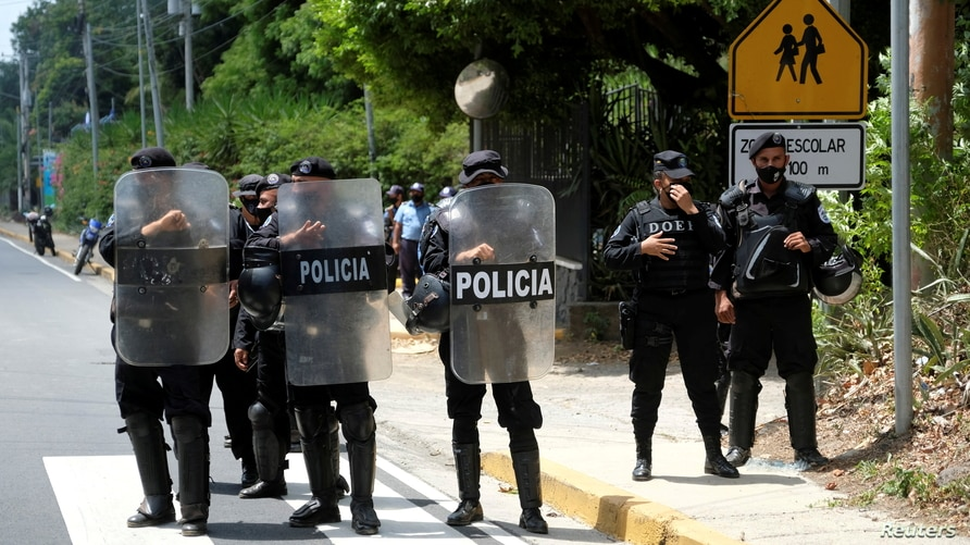 FILE PHOTO: Nicaraguan police officers stand in formation as they block journalists working outside the house of opposition…