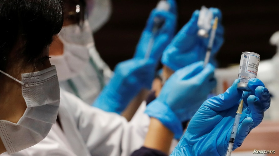 Healthcare workers prepare doses of the Moderna coronavirus disease (COVID-19) vaccine before administering them to staffers of…