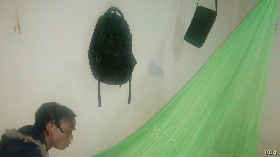 A lady in Malawi is seen spreading a mosquito net. Statistics show that only 55% of Malawians use mosquito nets to protect against Malaria. (Lameck Masina/VOA)
