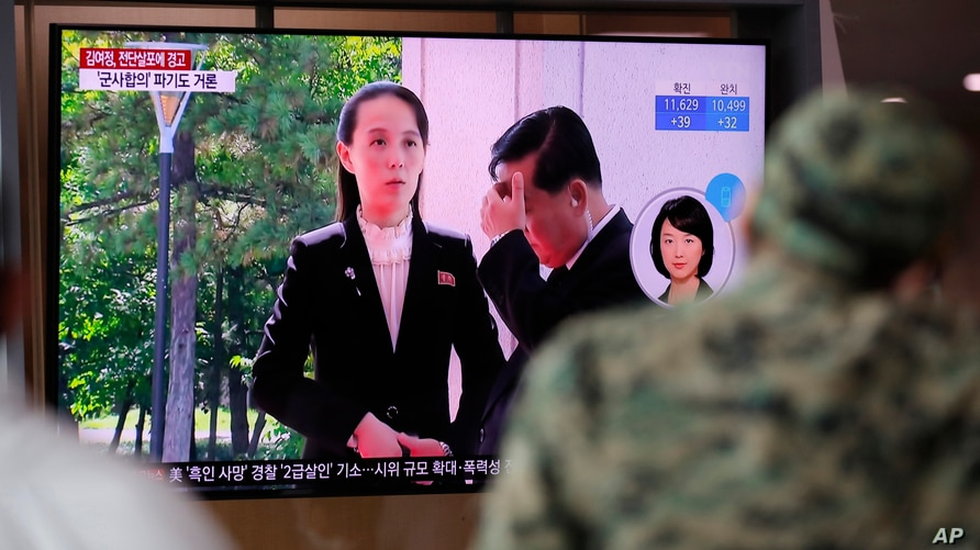 FILE - A man watches a TV screen showing a news program with a file image of Kim Yo Jong, the powerful sister of North Korea's leader.