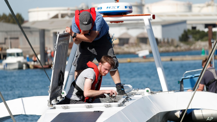 FILE - Technicians check the hull and interior of the Mayflower Autonomous Ship at its launch site for it's first outing on water since being built in Turnchapel, Plymouth south west England, Sept. 14, 2020.