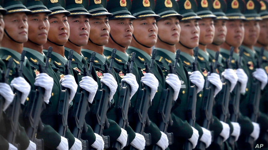 In this Oct. 1, 2019, photo, Chinese People's Liberation Army (PLA) soldiers march in formation during a parade to commemorate…