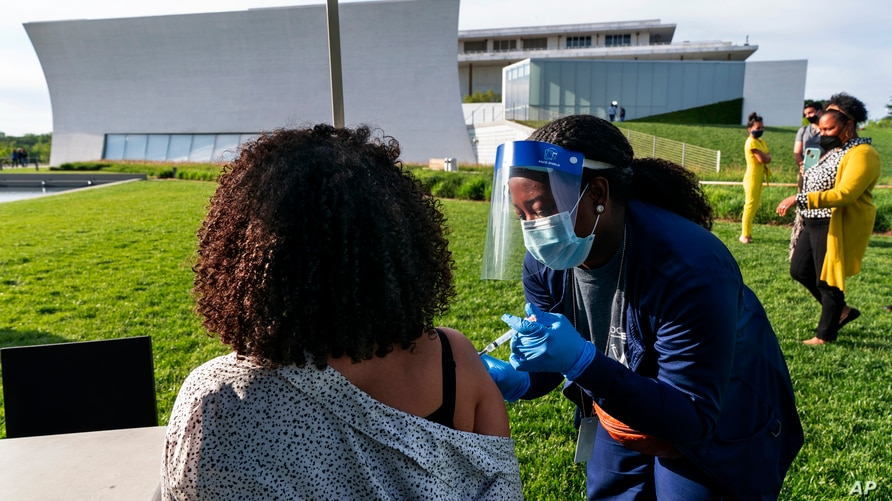 Kendria Brown, a nurse with DC health, vaccinates a woman with the J & J COVID-19 vaccine, Thursday, May 6, 2021, at The REACH…