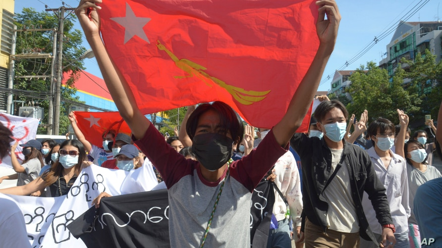Anti-coup protesters display a party flag of the National League for Democracy (NLD) during a demonstration in Yangon, Myanmar, May 14, 2021.