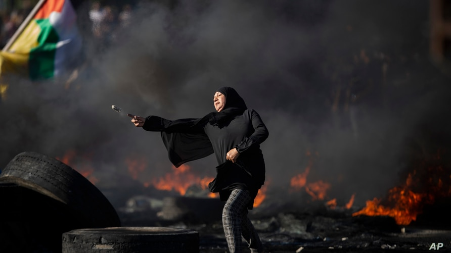 FILE - Palestinians clash with Israeli forces at the Hawara checkpoint, south of the West Bank city of Nablus, May 18, 2021.