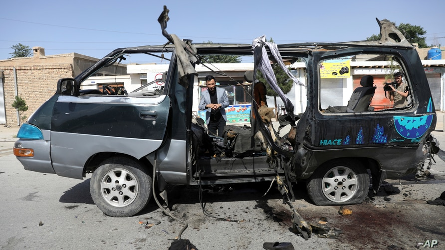 Afghan journalists film the site of a bomb explosion in Kabul, Afghanistan, June 3, 2021.