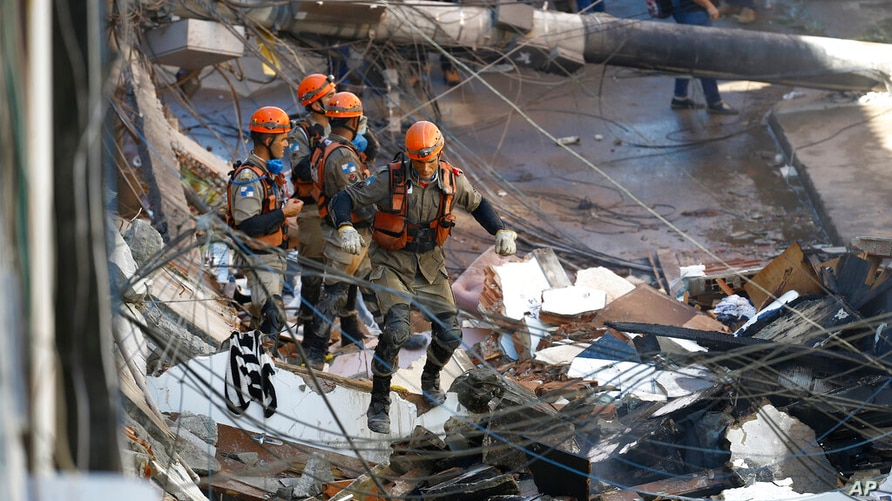 Firefighters search for survivors after pulling some from the debris of a four story building that collapsed overnight in the…