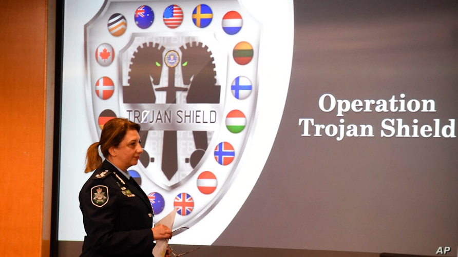 Commander Xenia Cotter, from the Australian Federal Police, walks past an Operation Trojan shield logo during a news conference…