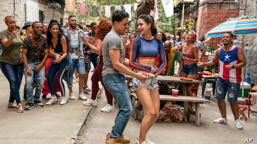 """This image released by Warner Bros. Picures shows Anthony Ramos, foreground left, and Melissa Barrera in a scene from """"In the…"""