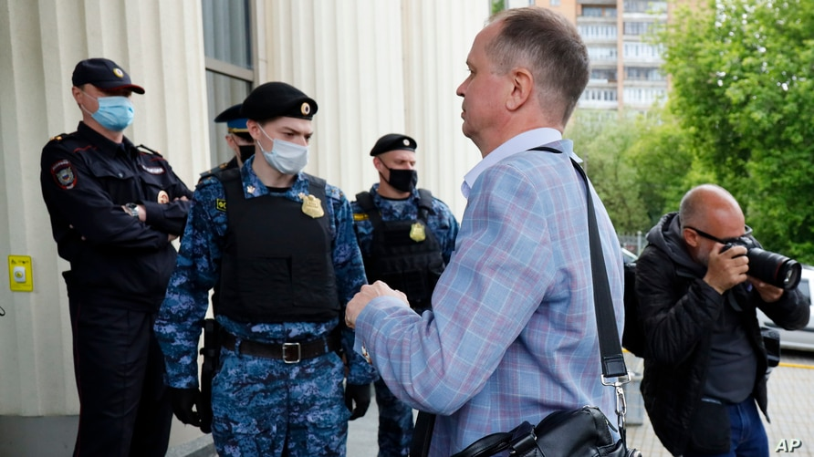 Russian lawyer Ivan Pavlov walks past police officers to attend a court session after speaking to the media at Moscow Court in Moscow, Russia, June 9, 2021.