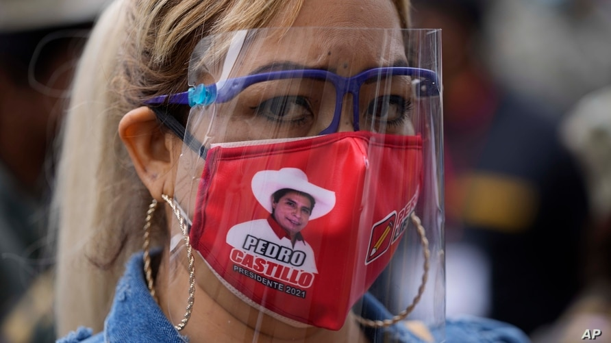 A supporter of presidential candidate Pedro Castillo wears a mask with Castillo's face during a march in Lima, Peru, June 9, 2021.
