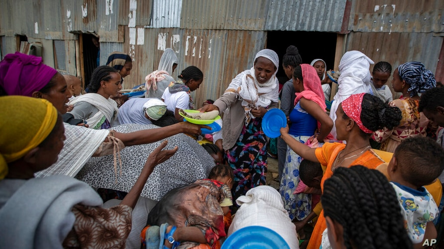 Displaced Tigrayans queue to receive food donated by local residents at a reception center for the internally displaced in…