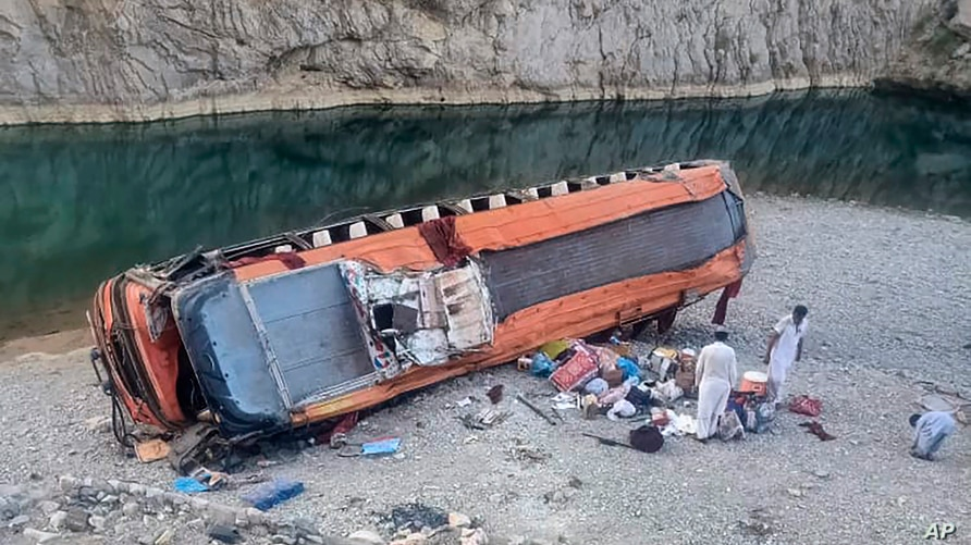 Locals gather supplies next to a damage bus at the site of accident in Khuzdar, a remote district in Pakistan