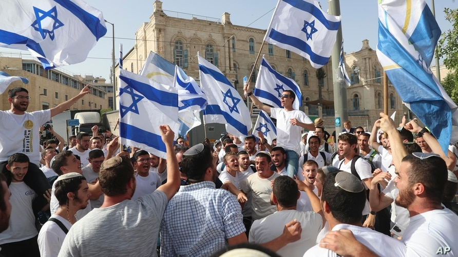 FILE - In this May 10, 2021, file photo, Israelis wave national flags during a Jerusalem Day parade, in Jerusalem. Israel's new…