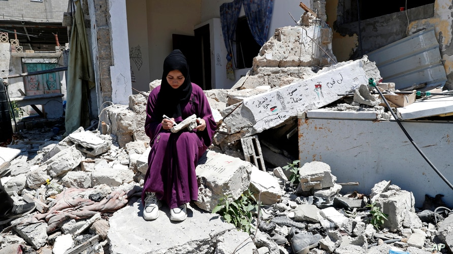 Artist Saja Moussa draws on broken tiles from her family's house in Rafah refugee camp, southern Gaza Strip,  June 15, 2021.