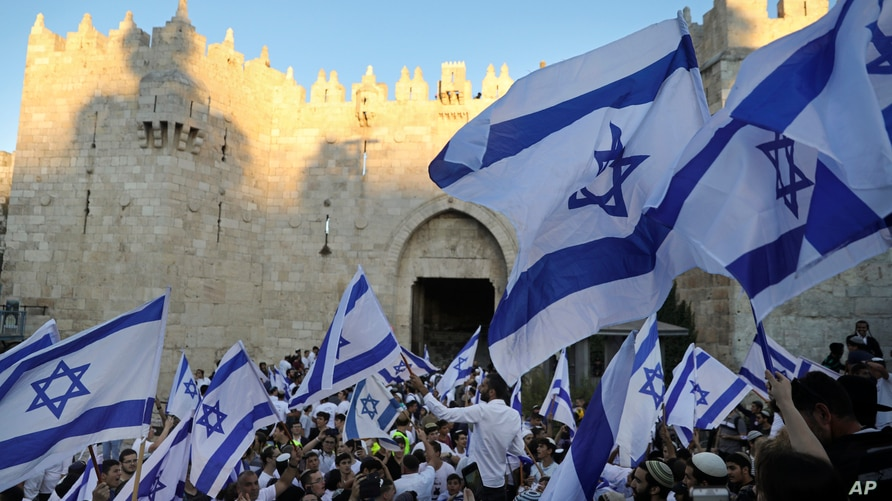"""Jewish ultranationalists wave Israeli flags during the """"Flags March,"""" next to Damascus gate, outside Jerusalem's Old City,…"""