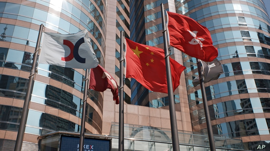 FILE - Flags are raised outside the Hong Kong Exchange Square building.