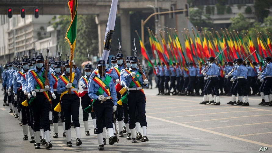 Ethiopian police holding national flags march during a parade to display new police uniforms and instruct them to maintain…