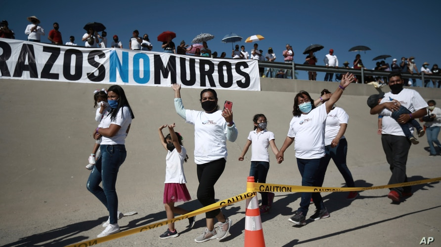 """Family members wave as they arrive to take part in the 8th annual """"Hugs not Walls"""" event on the Rio Grande, in Ciudad Juarez, Mexico, June 19, 2021."""