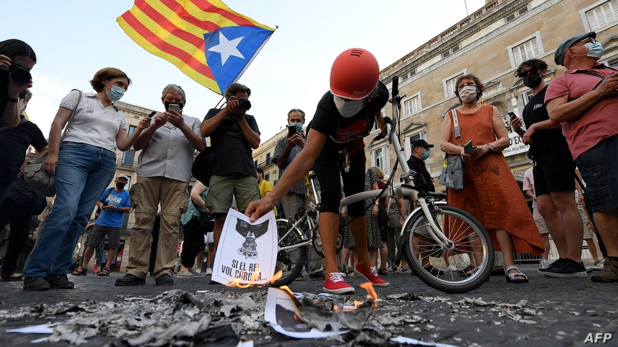 Anti-monarchy demonstrators burn pictures of the Spanish king during a protest against the visit of King Felipe VI of Spain to Catalonia, in Barcelona, June 15, 2021.