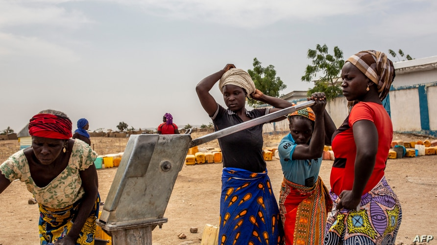Women fetch water at the Minawao refugee camp near Gadala, Cameroon, March 3, 2020.
